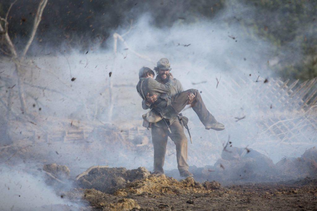 Newton (Matthew McConaughey) carries Daniel (Jacob Lofland) across an active battlefield